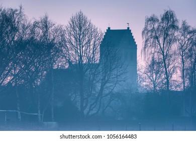 Historical church and winter trees in morning mist. Dutch rural village, Geesteren, Gelderland, Achterhoek.