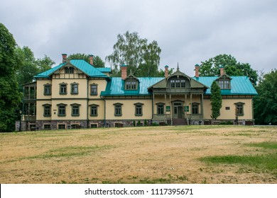 The historical colorful old mansion in the green park in Minsk. Dark sky of Belarus.