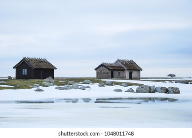 Historical fishermens cabins in an open winter landscape at the swedish island Oland in the Baltic Sea