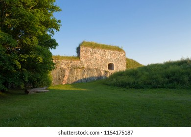 The historical fortifications on the island of Suomenlinna in the Gulf of Finland illuminate the setting sun on a summer evening.