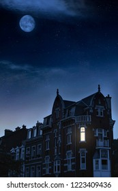 Historical houses with illuminated window under starry sky.