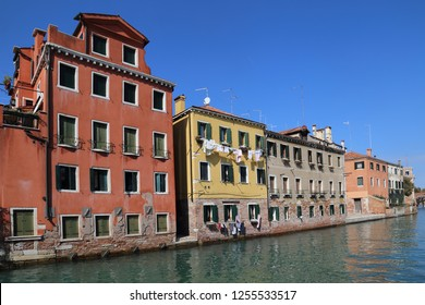 Historical houses with laundry hanging from windows along a canal looking towards the Arsenal in Venice, Italy