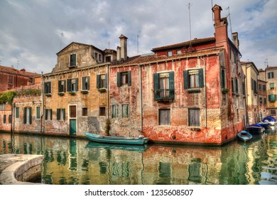 Historical houses on a canal with reflections and small boats in Venice, Italy