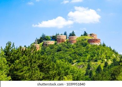 Historical Kutahya Castle with brick stone walls and bastions, at the hill surrounded with trees, on cloudy blue sky background.
