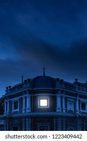 Historical mansion with illuminated window under dark sky at dusk.