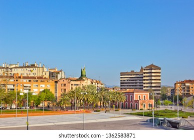 Historical and modern buildings seen across Railway Square in Girona, Spain