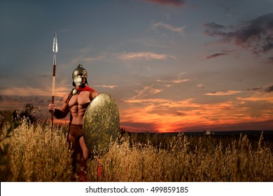 Historical moment. Horizontal shot of a muscular strong Spartan warrior in a helmet holding a spear and a shield standing in a field copyspace