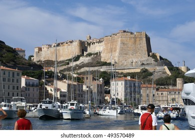 Historical monument Bastion de l'Etendard  overlooking the port of Bonifacio, pier with buildings, boats and yachts, some tourists in the foreground; Bonifacio (Bunifaziu), Corsica, France; 08/09/2014