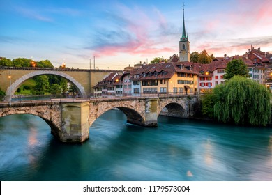 Historical Old Town of Bern city, tiled roofs, bridges over Aare river and church tower on dramatic sunset, Switzerland