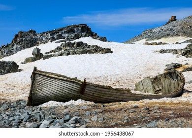 Historical old wooden boat abandoned and dilapidated on the rocky icy shore of Half Moon Island in the South Shetland Islands of Antarctica