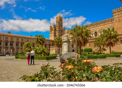 Historical Palermo Cathedral with hugging couple ot tourists the view thru beautiful mediterranean flowers with palm and beautiful sunny sky with clouds - Italy Sicily Aincient Europe