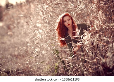 Historical reconstruction. Beautiful young woman with magnificent long red hair in a historical celtic dress looking out of the reeds.