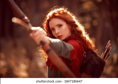 Historical reconstruction. Beautiful young woman archer with magnificent long red hair in a historical celtic dress stands outdoor.
