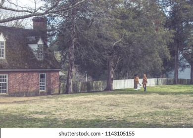 Historical reenactors walking beside colonial houses in Williamsburg, VA