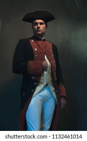 Historical regency man in hat holds hand in jacket.