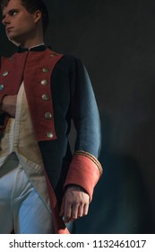 Historical regency man holds hand in jacket.