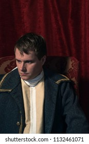 Historical regency man sits in front of red curtain.