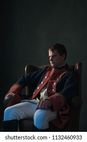 Historical regency man sitting in chair looking aside.