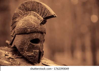 Historical Replica Spartan Warrior Helmet on pine forest background. Close up view of small miniature roman helmet