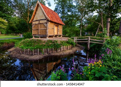 Historical shed in typical style with half-timbered structure and clay surrounded by a moat and idyllic greenery, blooming flowers and wooden bridge in the public spa park of Bad Zwischenahn (Germany)