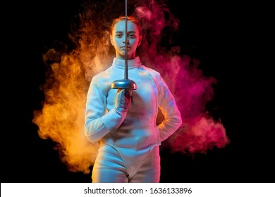 Historical time. Teen girl in fencing costume with sword in hand isolated on black background, neon lighted smoke. Practicing and training in motion, action. Copyspace. Sport, youth, healthy lifestyle