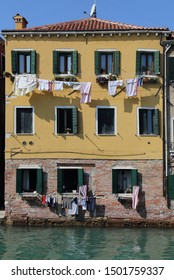 Historical Venetian home with washing hanging to dry from windows, on a canal in Venice, Italy