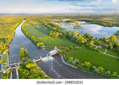 Historical water power plant building with the weir on the Labe River lock in Podebrady, Czech Republic. Aerial view on Old lock chamber in summer sunny color evening. Hydroelectric plant  - Shutterstock ID 1988510231