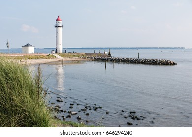 The historical white lighthouse with the characteristic red copper top at the shore of the Haringvliet at Hellevoetsluis in the southwest of Netherlands.