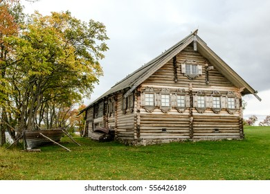 Historical wooden peasant house with an old boat under the tree, Kizhi, UNESCO world heritage site, Onega lake, Karelia, Russian north-west