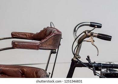 History of transport. Vintage powered bicycle. Close-up of retro handlebars and passenger seat. Actually a quadricycle because it would have had four wheels and an engine.
