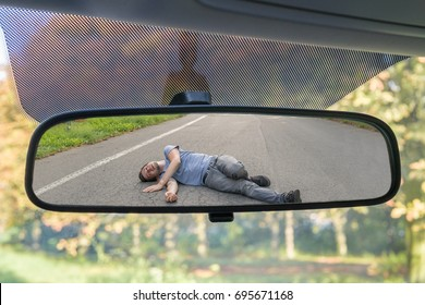 Hit and run concept. View on injured man on road in rear mirror of a car.