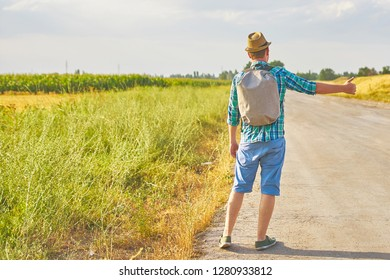 Hitchhiker with backpack in summer hat, light shirt, shorts on the road in tropical country in Sunny weather at summer
