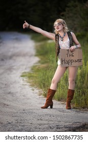 Hitchhiker girl. Young woman hitchhiker stands on the side of the road and holds a plate with the inscription in his hands