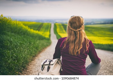 hitch-hiker woman sitting on a road and waiting for car, woman sitting on a road in the middle of countryside. Traveler resting during trip. Travel concept