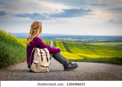 Hitch-hiker woman sitting on a road and waiting for car. Adventure on a journey