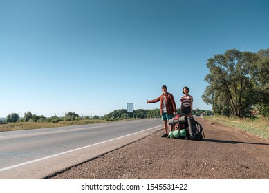 Hitchhiking couple. Backpackers on road.