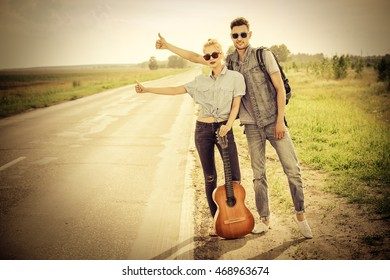 Hitchhiking couple. Romantic young people standing on a highway and catching a passing car. Sepia, retro styled.