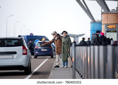 Hitchhiking. Full length of stylish senior couple is standing near road and trying to catch transport. Gentleman is rising hand while lady is looking at camera and holding her luggage confidently