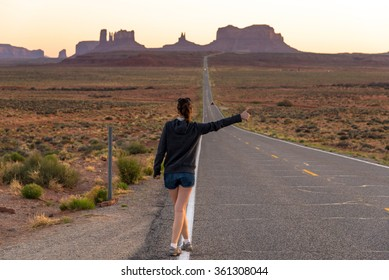 Hitchhiking girl on the road to Monument valley