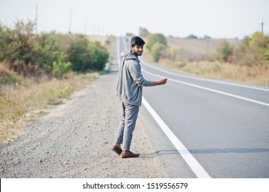 Hitchhiking indian man travelling by hitchhike on road side on highway.