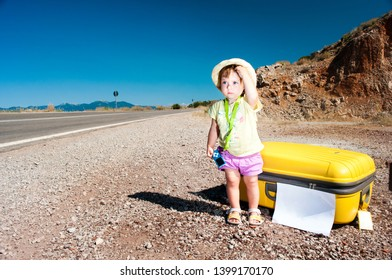 Hitchhiking. Little baby with a big yellow suitcase standing by the side of the road. Travel, tourism and summertime concept