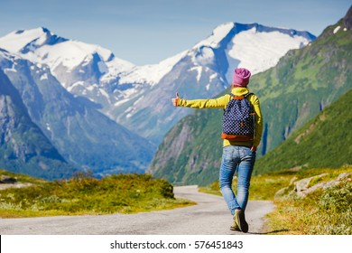 Hitchhiking tourism concept. Travel hitchhiker woman walking on road during holiday travel