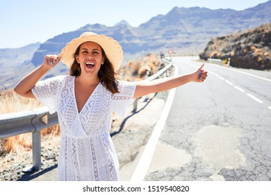 Hitchhiking woman travelling by hitchhike on road side, smiling happy on summer vacation