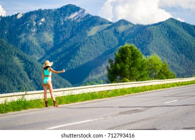 Hitchhiking young woman in bikini and sunhat on empty road