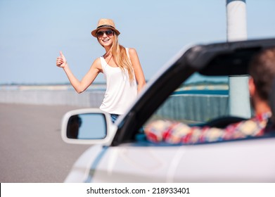 Hitching a ride. Beautiful young funky woman hitch-hiking on the side of the road with car on foreground