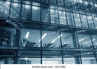 Hi-tech glass elevation of a modern office building at night with the lights turned on and the interior visible - office chairs and tables behind the windows