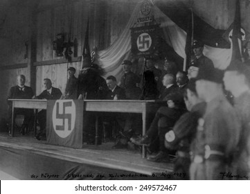 Hitler with members of the NSDAP sitting on stage, 1927. The figures siding beside Hitler are crayoned over. Nationalsozialistische Deutsche Arbeiterpartei National Socialist German Workers' Party.
