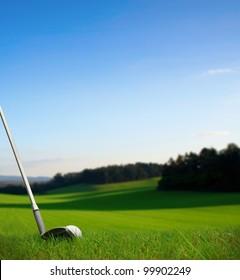hitting golf ball with club along fairway towards green