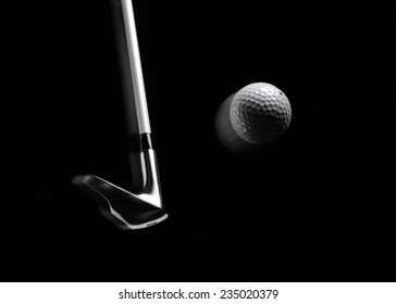 Hitting a golf ball in a mid air position, with a golf club isolated on black with copy space and blurred motion.