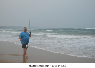 Hluhluwe , South Africa - Sep 24 2018:An elderly happy man caught a fish on a manual fishing rod  in Sodwana bay which is a pristine beach near a lagoon and Isimangaliso wetlands during summer